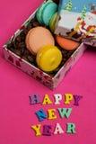Etikettieren Sie guten Rutsch ins Neue Jahr, Makronen mit Kaffeebohnen in der Geschenkbox Stockbild