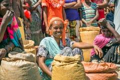 Etiopisk kvinna som säljer skördar i en lokal trängd ihop marknad Arkivfoto