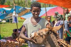 Etiopisk pojke med hans åsna på en marknad i Etiopien Arkivbild