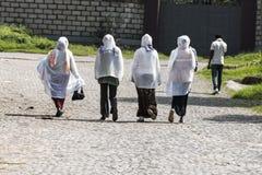 Etiopiska ortodoxa kvinnor som bär vita uddar som heading in mot kyrka i Addis Ababa Ethiopia Arkivfoto