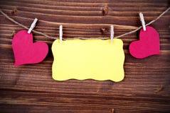 Etiqueta amarilla con el espacio de la copia y dos corazones y marcos Foto de archivo libre de regalías