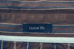 Etiqueta apta de la aduana en una camisa del hombre Fotos de archivo libres de regalías