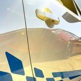 Etiqueta azul en un coche blanco iluminado por el sol con reflexiones imagenes de archivo
