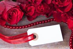 Etiqueta blanca con las rosas rojas Imagenes de archivo