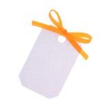 Etiqueta blanca del regalo con el arqueamiento anaranjado de la cinta Fotografía de archivo libre de regalías