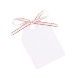 Etiqueta blanca del regalo con el arqueamiento de la cinta Fotografía de archivo