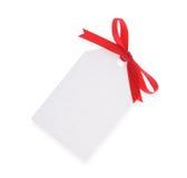 Etiqueta blanca del regalo con el arqueamiento rojo Foto de archivo libre de regalías