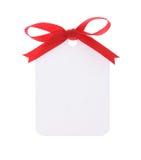 Etiqueta blanca del regalo con el arqueamiento rojo fotografía de archivo libre de regalías