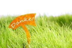 Etiqueta com alemão Danke que os meios lhe agradecem na grama verde Fotografia de Stock Royalty Free