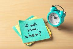 """Etiqueta com frase \ """"se não agora, quando? \"""" e despertador na tabela Conceito da gest?o de tempo foto de stock royalty free"""