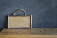 Etiqueta con el marco de madera en el piso y el fondo de madera del cemento Fotos de archivo libres de regalías
