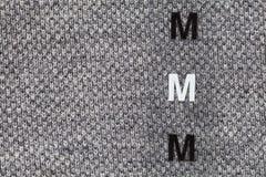 Etiqueta con la talla plástica en la camisa Foto de archivo