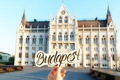 Etiqueta da rotulação de Budapest em uma mão e construção húngara do parlamento no fundo Foto de Stock Royalty Free