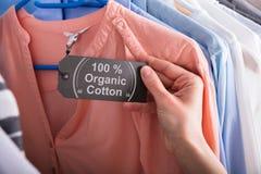 Etiqueta da terra arrendada da mulher que mostra 100 por cento de algodão orgânico fotografia de stock royalty free