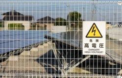 Etiqueta de advertencia japonesa al lado de la granja solar Foto de archivo libre de regalías