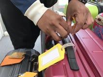 Etiqueta de couro amarela em uma mala de viagem vermelha imagens de stock royalty free