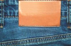 Etiqueta de cuero marrón en blanco en los tejanos Foto de archivo