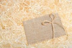 Etiqueta de la arpillera en fondo de la paja. Imagen de archivo libre de regalías