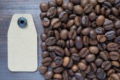Etiqueta de la cartulina cerca de los granos de café Imagenes de archivo