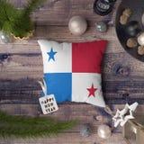 Etiqueta de la Feliz Año Nuevo con la bandera de Panamá en la almohada Concepto de la decoraci?n de la Navidad en la tabla de mad imagen de archivo