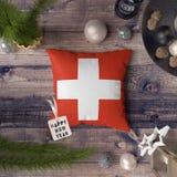 Etiqueta de la Feliz Año Nuevo con la bandera de Suiza en la almohada Concepto de la decoraci?n de la Navidad en la tabla de made imagen de archivo libre de regalías