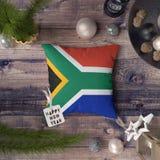 Etiqueta de la Feliz Año Nuevo con la bandera de Suráfrica en la almohada Concepto de la decoraci?n de la Navidad en la tabla de  fotos de archivo