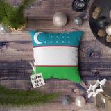 Etiqueta de la Feliz Año Nuevo con la bandera de Uzbekistán en la almohada Concepto de la decoraci?n de la Navidad en la tabla de foto de archivo