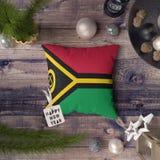 Etiqueta de la Feliz Año Nuevo con la bandera de Vanuatu en la almohada Concepto de la decoraci?n de la Navidad en la tabla de ma foto de archivo libre de regalías