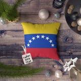 Etiqueta de la Feliz Año Nuevo con la bandera de Venezuela en la almohada Concepto de la decoraci?n de la Navidad en la tabla de  foto de archivo