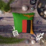 Etiqueta de la Feliz Año Nuevo con la bandera de Zambia en la almohada Concepto de la decoraci?n de la Navidad en la tabla de mad foto de archivo libre de regalías