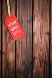 Etiqueta de la Feliz Navidad en superficie de madera Foto de archivo libre de regalías