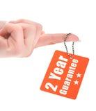 Etiqueta de la garantía de la tenencia de la mano Fotografía de archivo libre de regalías