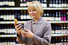Etiqueta de la lectura de la mujer en la botella de vino en tienda Imagen de archivo libre de regalías