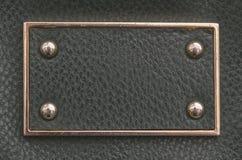Etiqueta de la piel artificial con la frontera y los remaches del metal Imágenes de archivo libres de regalías