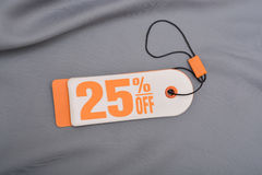 Etiqueta de la venta que pone letras al 25 por ciento apagado con el fondo de seda Fotos de archivo