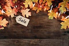 Etiqueta de las hojas y de las ventas de la caída sobre fondo de madera Imagenes de archivo