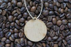 Etiqueta de madera del círculo puesta en los granos de café Imagenes de archivo