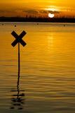 Etiqueta de plástico del río silueteada contra el sol de configuración Foto de archivo
