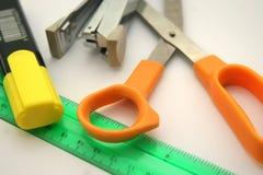 Etiqueta de plástico, regla, tijeras y grapadora Fotografía de archivo libre de regalías