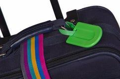 Etiqueta del equipaje y correa colorida en la maleta Fotos de archivo