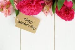 Etiqueta del regalo del día de madre con las flores en la madera blanca Fotografía de archivo