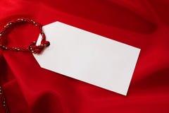 Etiqueta del regalo en el satén rojo Imágenes de archivo libres de regalías