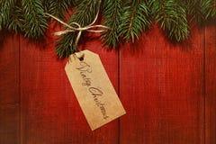 Etiqueta del regalo en fondo de madera rojo Fotografía de archivo libre de regalías