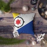 Etiqueta do ano novo feliz com a bandeira de Bonaire no descanso Conceito da decora??o do Natal na tabela de madeira com objetos  foto de stock