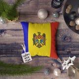 Etiqueta do ano novo feliz com a bandeira de Moldova no descanso Conceito da decora??o do Natal na tabela de madeira com objetos  foto de stock royalty free