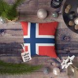 Etiqueta do ano novo feliz com a bandeira de Noruega no descanso Conceito da decora??o do Natal na tabela de madeira com objetos  fotografia de stock royalty free