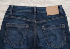 A etiqueta do couro de Brown da calças de ganga suporta sobre do brim imagem de stock