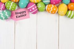 Etiqueta do presente com beira da parte superior do ovo da páscoa contra a madeira branca Imagem de Stock