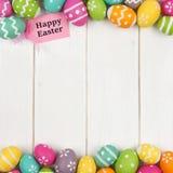 Etiqueta do presente com beira do dobro do ovo da páscoa contra a madeira branca Fotografia de Stock