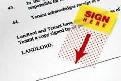 A etiqueta do sinal-aqui no contrato rental Imagem de Stock Royalty Free